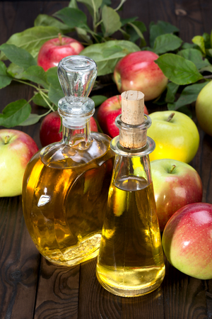 apple cider vinegar in a glass vessel and red apples isolated on wood background Stock Photo