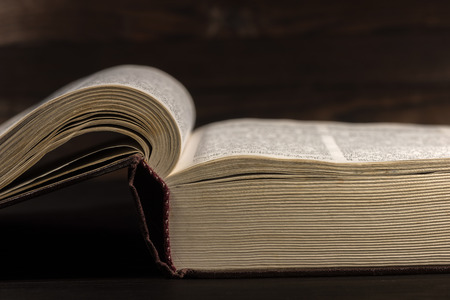 The old open book - the Holy Bible on a dark wooden background