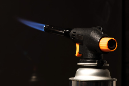 gas burner: gas burner - burning tool with a blue flame. low key Stock Photo
