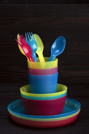 colored plastic tableware on a dark wooden background - color CMYK Stock Photo
