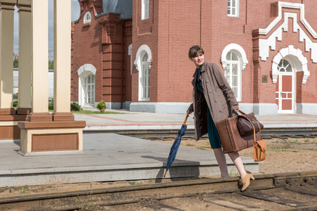 Young woman walks on rails at a train station with luggage