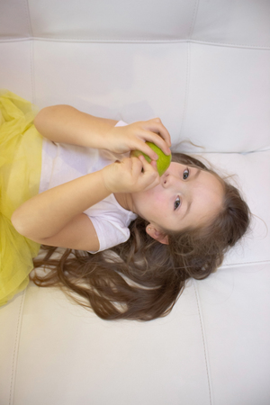 happy girl holding and eating yellow sweet pear