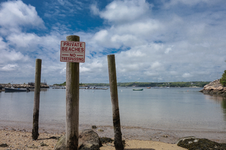 trespassing: No trespassing sign on the wooden post at shore in MA, USA Stock Photo