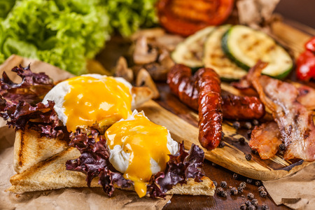 benedict: English breakfast with poached eggs, sausages, bacon, vegetable and spices