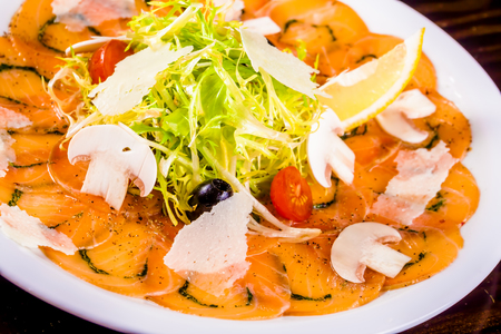 Appetizer. Salmon carpaccio with parmesan cheese on white plate
