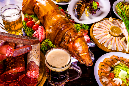 Food table. Roasted piglet, grilled fish, cold-boiled pork, beer and appetizers Stock Photo
