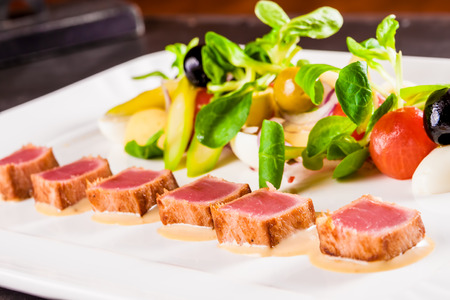 Nicoise salad with tuna, vegetables and herbs on white plate
