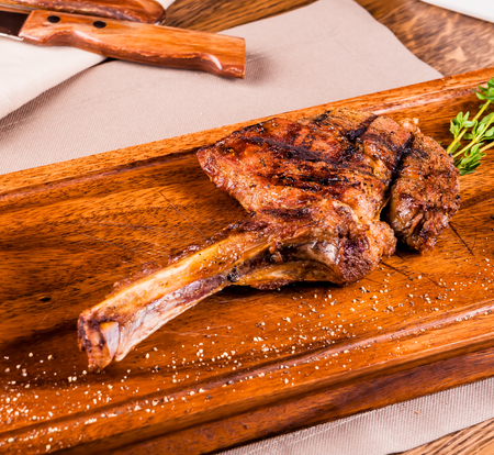 Grilled rack of lamb on wooden board