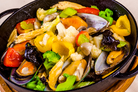 Mussels with vegetables in cast-iron black pot