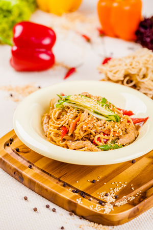 Noodles with vegetables and chicken in beige plate on wooden board