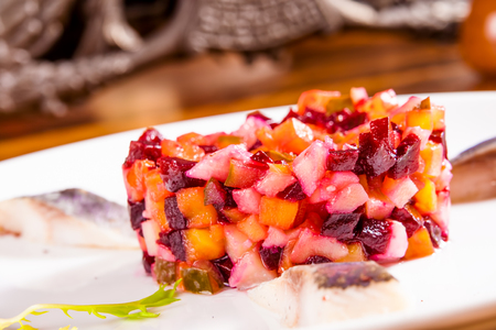 Russian beetroot salad with herring on white plate