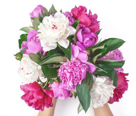 Ramo de flores de peonía rosadas y blancas en mano de mujer aislado sobre fondo blanco. Vista superior. Endecha plana.