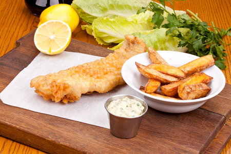 Fish and chips with sauce on wooden cutting board. Close up Stock Photo