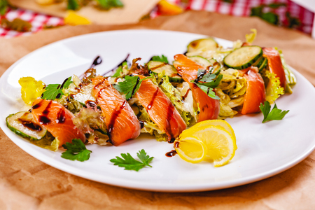 Salad with salmon, cucumber and mixed greens on white plate. Close up