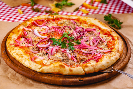 Pizza with tuna and red onion on wooden cutting board. Close up Imagens