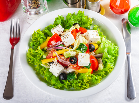 Greek salad with vegetables on white plate. Close up