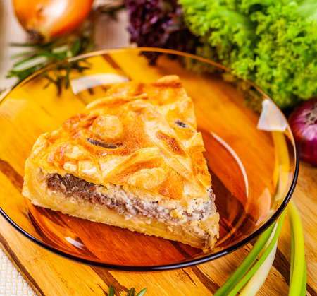 Meat pie with potato and onion in glass bowl