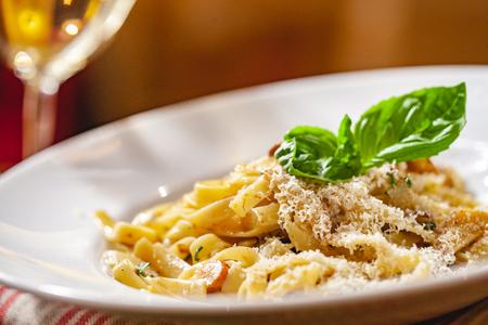 Pasta italiana con funghi e parmigiano su piatto bianco. Avvicinamento