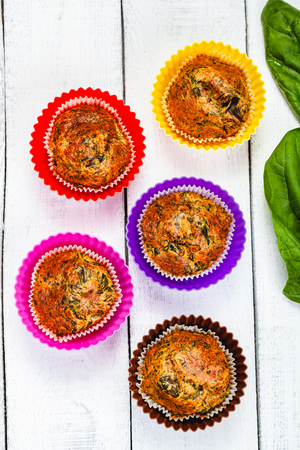 Muffins with basil and spinach on wooden rustic table. Close up. Top view