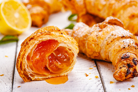 Croissants with lemon jam on white wooden background. Close up