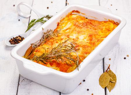 Zapiekanka ziemniaczana w białym naczyniu żaroodpornym na drewnianym stole w stylu rustykalnym. Ścieśniać