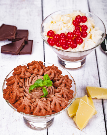 Homemade chocolate mousse in portion glasses on wooden background. Close up