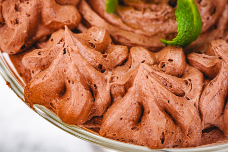 Homemade chocolate mousse in portion glass on wooden background. Close up
