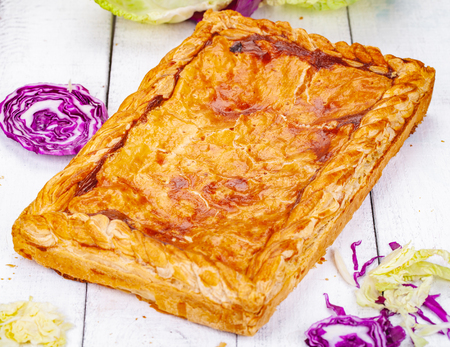Pie with cabbage on wooden rustic table. Close up