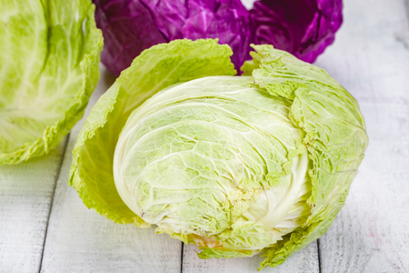 Green and red heads of cabbage on wooden background. Close up Zdjęcie Seryjne