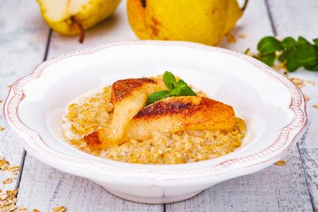 Oatmeal porridge with pear in white plate. Close up Zdjęcie Seryjne