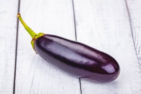 Fresh raw eggplant on wooden background. Close up Imagens