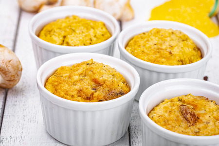 Polenta with mushrooms in white ramekin bowls on wooden rustic table. Close up