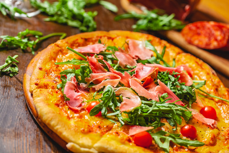 Italian pizza with prosciutto (parma ham), arugula (salad rocket) and cherry tomatoes on wooden board. Close up