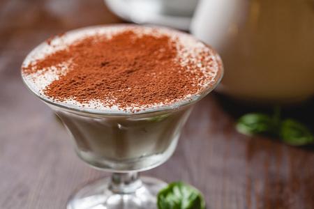Italian dessert Tiramisu in portion glass on wooden table. Close up