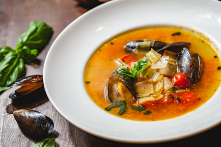 Soup with mussels and vegetables in white plate on wooden table. Close up