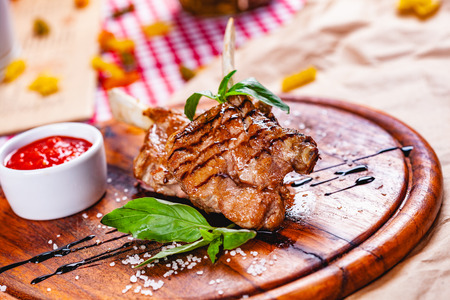 Rack of lamb fried with aromatic olive oil, herbs and spices on wooden board. Close up Zdjęcie Seryjne