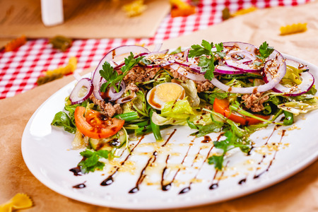 Salad with meat, egg, vegetables on white plate. Close up Zdjęcie Seryjne