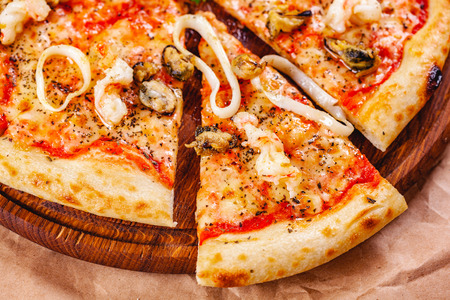 Italian Pizza with seafood and mozzarella cheese on wooden cutting board. Close up