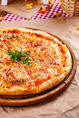 Italian Pizza with bacon, tomatoes and mozzarella cheese on wooden cutting board. Close up Zdjęcie Seryjne