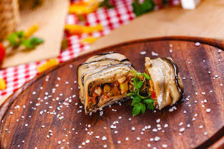 Eggplant roll filled with vegetables on wooden cutting board. Close up