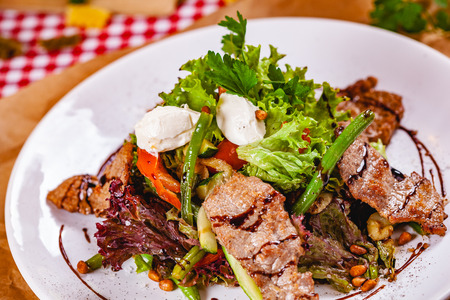 Salad with fried meat, pine nuts, vegetables and mozzarella cheese on white plate. Close up Zdjęcie Seryjne