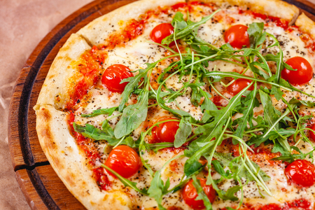 Italian Pizza with tomatoes, mozzarella cheese and arugula on wooden cutting board. Close up
