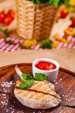 Rack of lamb with tomato sauce on wooden cutting board. Close up Zdjęcie Seryjne - 121183663