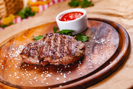 Grilled beef steak with tomato sauce on wooden cutting board. Close up Zdjęcie Seryjne - 121183666