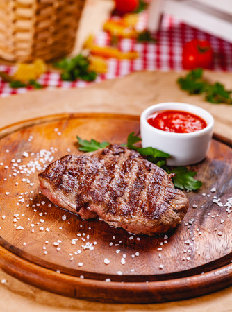 Grilled beef steak with tomato sauce on wooden cutting board. Close up