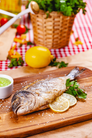 Grilled dorado fish with lemon and sauce on wooden board. Close up Zdjęcie Seryjne - 121183673