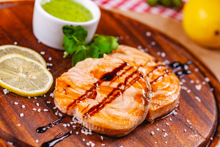 Grilled fish steak served with sauce and lemon on wooden cutting board. Close up Zdjęcie Seryjne - 121183680