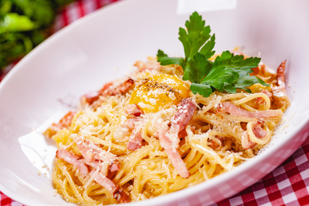 Spaghetti Carbonara with bacon, yolk and cheese on white plate. Close up Zdjęcie Seryjne