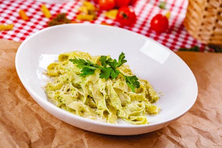 Italian Pasta tagliatelle with pesto sauce and parmesan cheese on white plate. Close up Zdjęcie Seryjne - 121183684