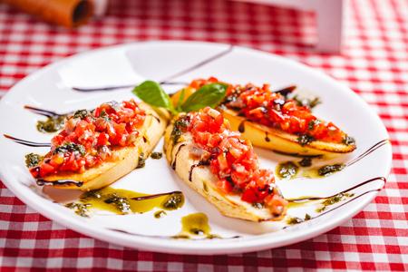 Traditional Italian bruschetta with cherry tomatoes, pesto sauce and balsamic vinegar on white plate. Close up